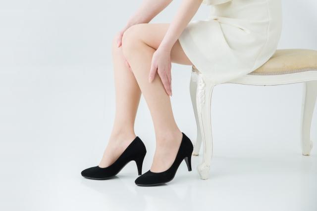 足を気にする女性の写真
