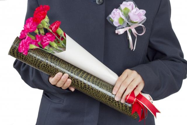 卒業証書と花をもつ生徒の胸下あたりの写真