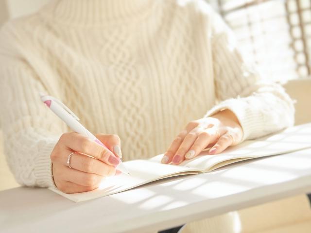 ノートにメモを取る女性のイメージ写真