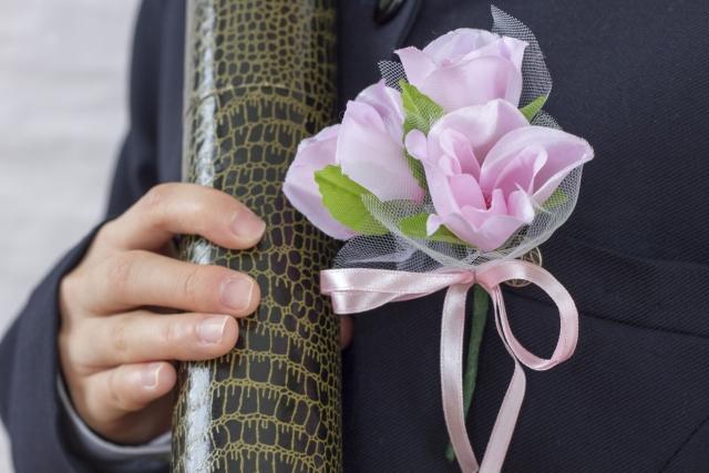 卒業証書をもつ胸に薔薇をつけた生徒の写真