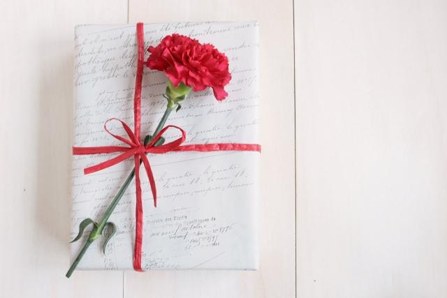 カーネーションが刺さったプレゼントボックスの写真