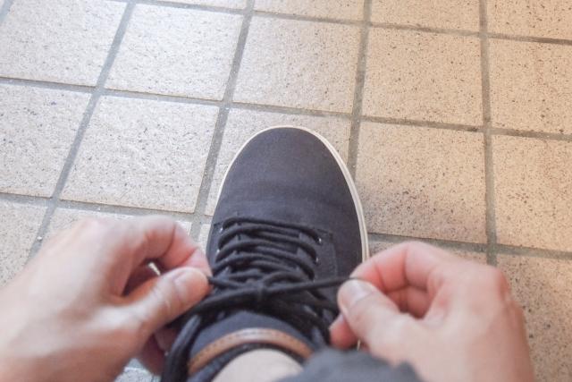 靴ひもを結ぶ手の写真
