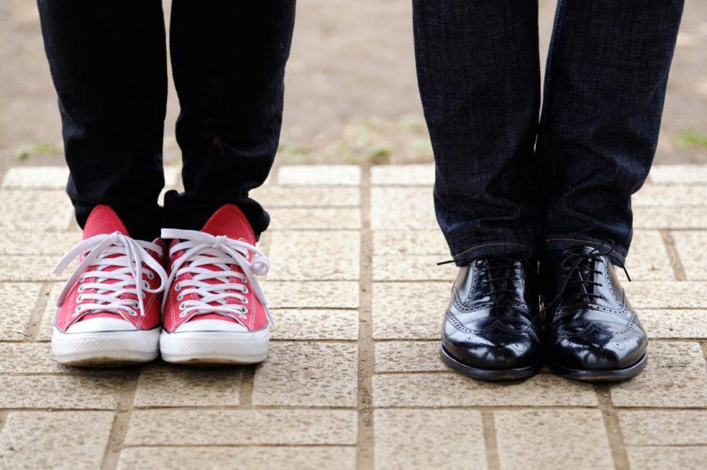 スニーカーを履いている人と革靴を履いている人の写真
