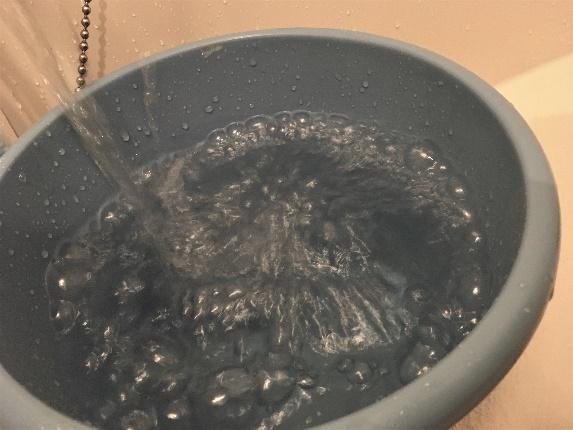 バケツにお湯を溜めている写真