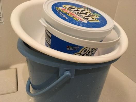 バケツに洗面器で蓋をしてオキシクリーンを重しにしている写真