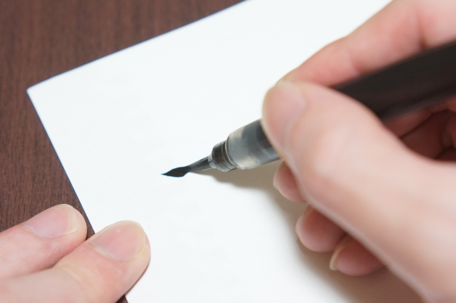 筆ペンで字を書く写真
