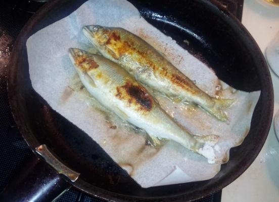 フライパンで魚を焼いている写真