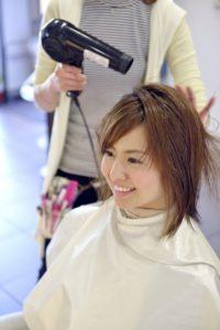 髪を乾かしてもらっている女性