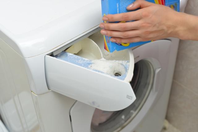 洗剤を洗濯機にいれている写真