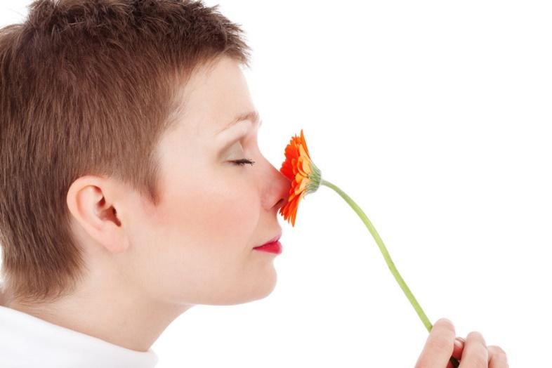 花の香りを嗅ぐ人