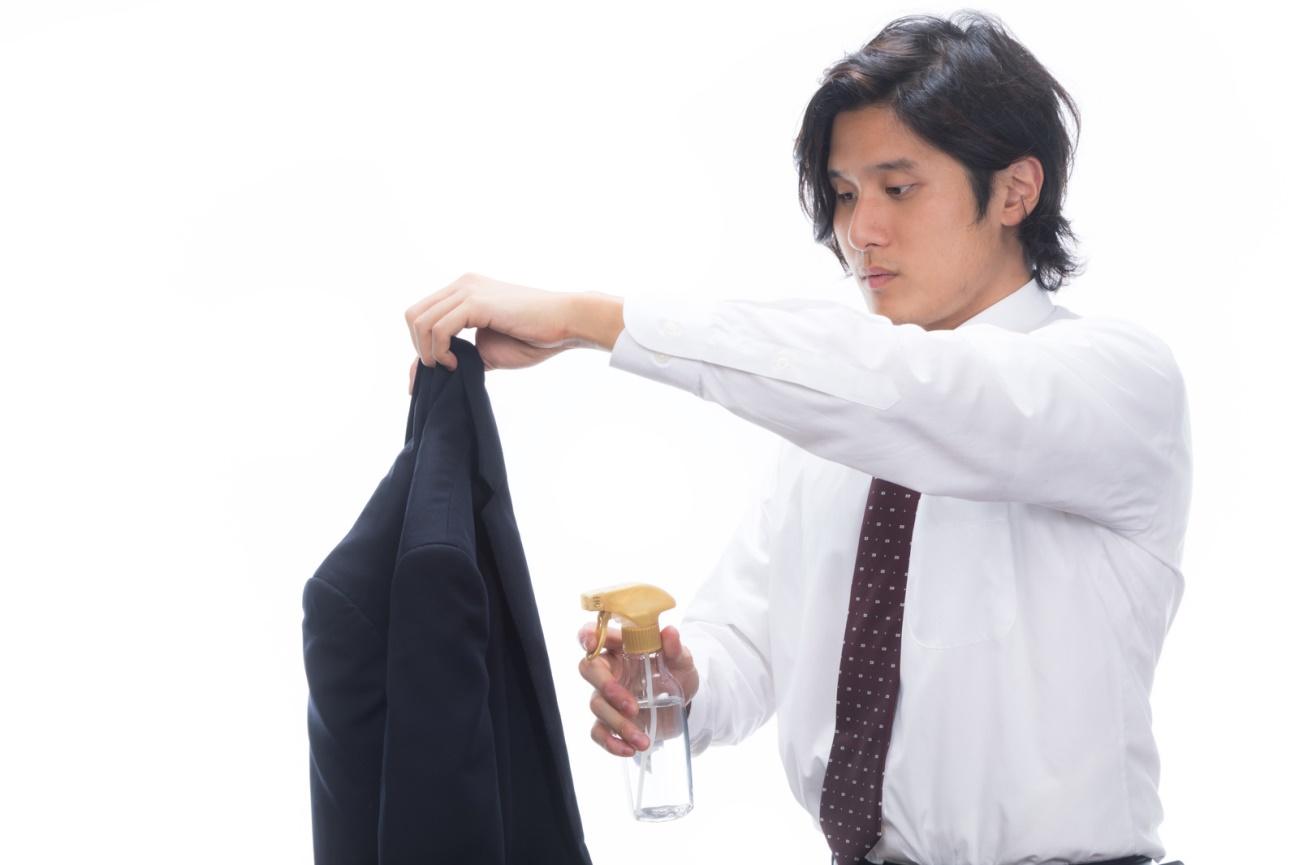 消臭スプレーをスーツにかける男性