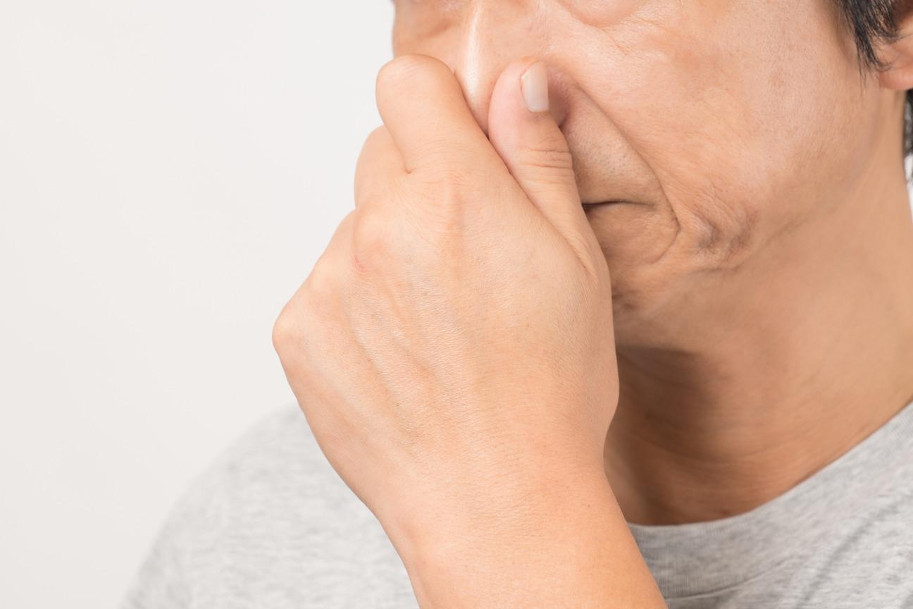 鼻をつまむ人